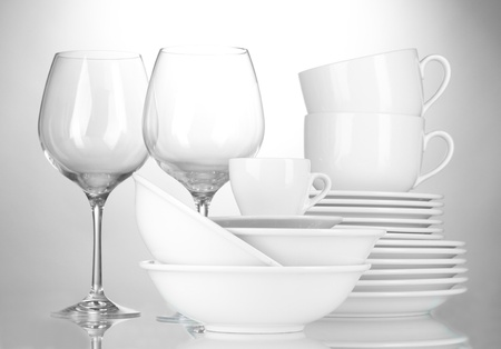 dinnerware: empty bowls, plates, cups and glasses on grey background Stock Photo
