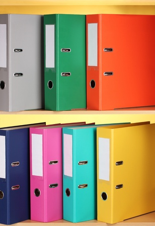 bright office folders on wooden shelfs on yellow background photo