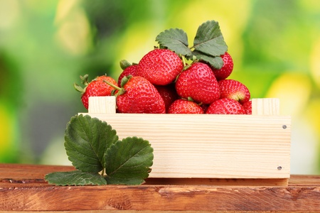 Strawberries with leaves in wooden box on table on green  background photo