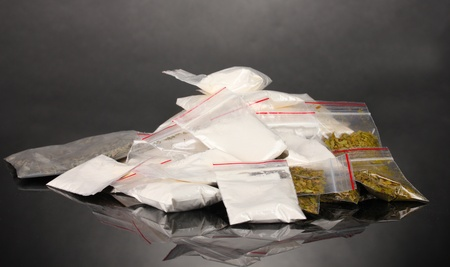 methamphetamine: Cocaine and marihuana in packages on grey background Stock Photo