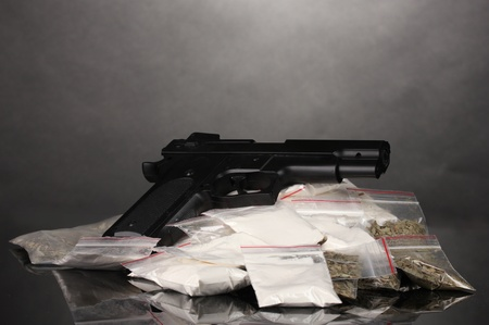 street drug: Cocaine and marihuana in packages and handgun on grey background Stock Photo