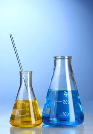 Two flasks with yellow and blue liquid with reflection on blue background Stock Photo - 12098100