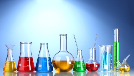 clinical research: Different laboratory glassware with color liquid and with reflection on blue background