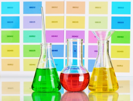 Three flasks with color liquid on color samples background photo