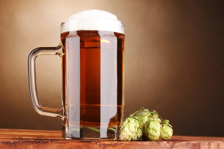 beer mug and green hop on wooden table on brown background photo