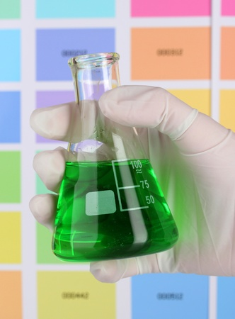 Flask with green liquid in hand on color samples background Stock Photo - 12098152