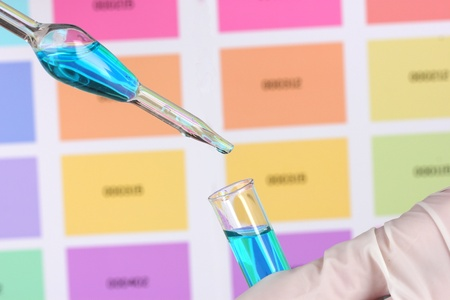 Test-tube with blue liquid and pipette in scientists hands on color samples background photo