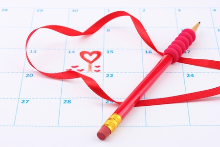 Calendar page with hearts, pencil and ribbon on St.Valentines Day photo