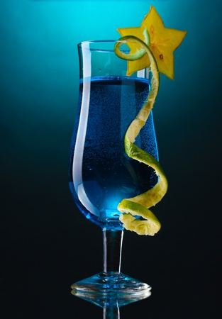 Blue cocktail in glass on blue background photo