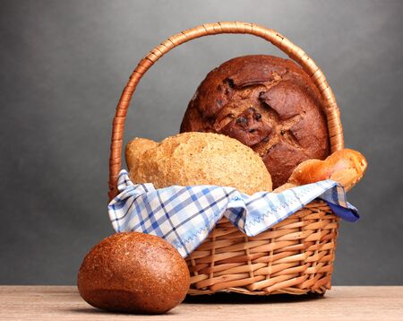 delicious bread in basket on wooden table on gray background Stock Photo - 12134261