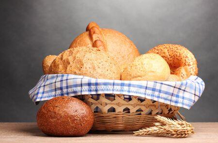canasta de pan: delicioso pan en la canasta y las orejas en la mesa de madera sobre fondo gris