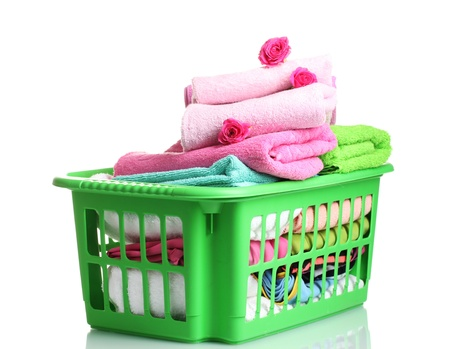 Towels in green plastic basket isolated on white photo