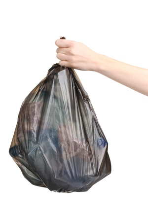 black garbage bag with trash in hand isolated on white photo