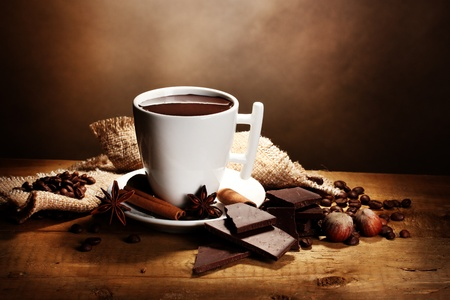 cup of hot chocolate, cinnamon sticks, nuts and chocolate on wooden table on brown background photo
