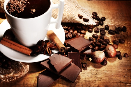 hot cocoa: cup of hot chocolate, cinnamon sticks, nuts and chocolate on wooden table Stock Photo