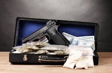 illicit: Cocaina, marijuana e pistola dollari nel caso in cui su tavola di legno su sfondo grigio