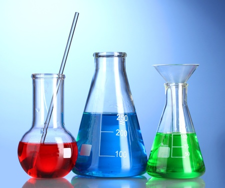 Three flasks with color liquid with reflection on blue background photo