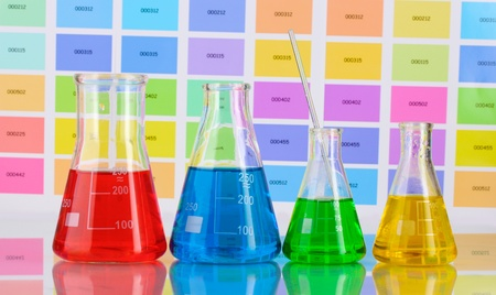 Laboratory flasks with color liquid on color samples background photo