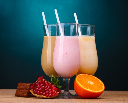 Milk shakes with fruits and chocolate on wooden table on blue background photo