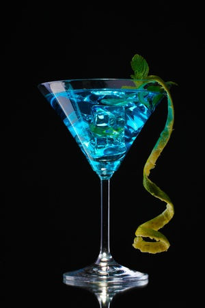Blue cocktail in glass on black background photo