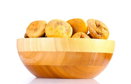 delicious dried figs in wooden bowl isolated on white photo