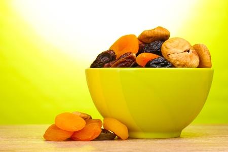 frutas secas: Los frutos secos en un tazón verde en la mesa de madera sobre fondo verde Foto de archivo