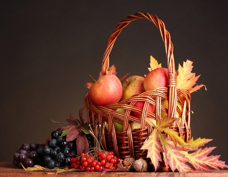 beautiful autumn harvest in basket and leaves on brown background photo