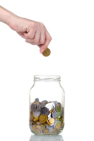 generosidad: Banco de vidrio para las extremidades con el dinero y la mano aislado en blanco