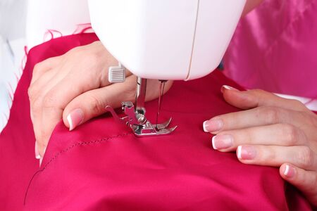 sewing machine, red fabric and womens hands photo