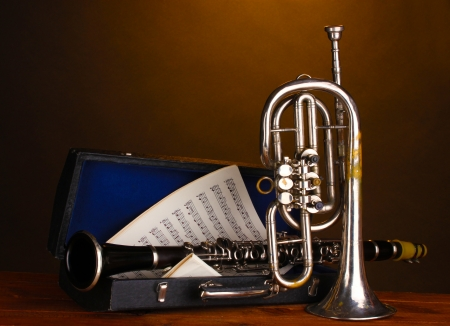 fanfare: antique trumpet and clarinet in case on wooden table on brown background