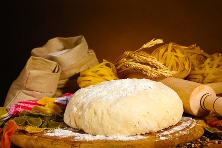dough: ingredientes para la pasta hecha en casa en la mesa de madera sobre fondo marrón