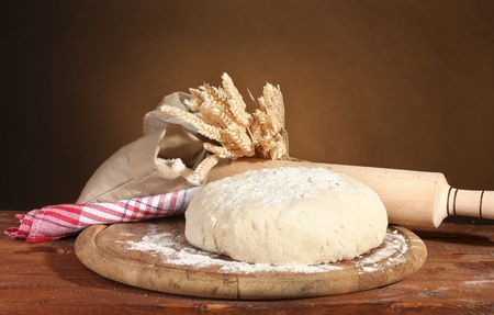 Dough and bags with flour on wooden table on brown background photo