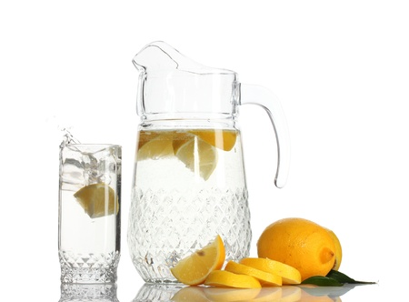pitcher and glass of lemonade and lemon isolated on white photo