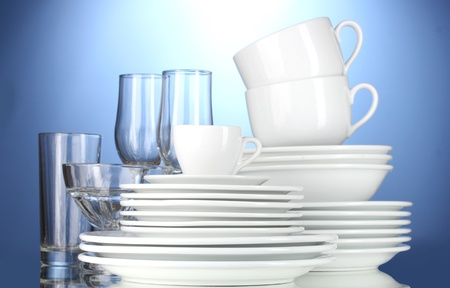 clean dishes: empty bowls, plates, cups and glasses on blue background