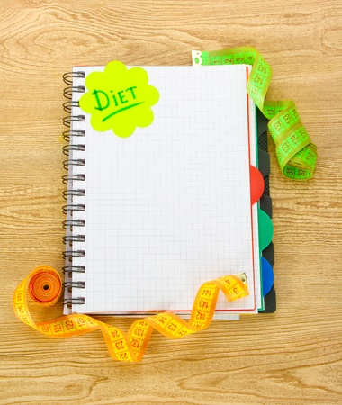 Planning of diet. Notebook measuring tapes and pen on wooden table photo