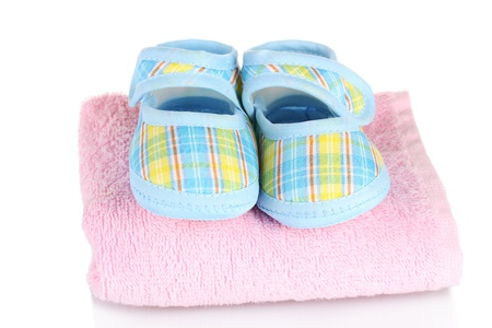 Blue baby booties on pink towel isolated on white photo