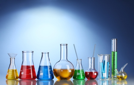 green chemistry: Different laboratory glassware with color liquid and with reflection on blue background