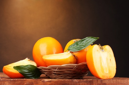 Appetizing persimmons in pad on wooden table on brown background