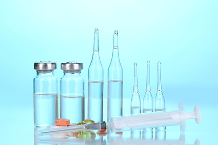 Syringe with medical ampoules and tablets on blue background photo
