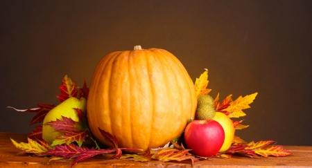 pumpkin, apples and leaves on wooden table on brown background photo