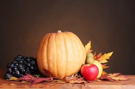 pumpkin, apples, grapes and leaves on wooden table on brown background photo
