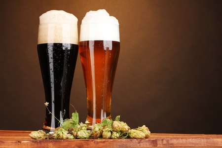 black and golden beer in glasses and hop on wooden table on brown background photo