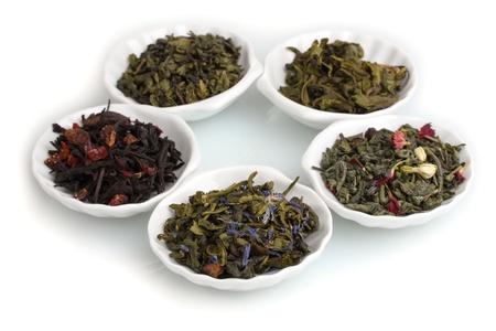 Hojas secas de té verde y negro en placas aisladas en blanco Foto de archivo
