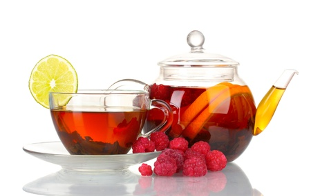 Black fruit tea in glass teapot and cup isolated on white