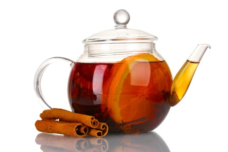 Glass teapot with black tea of orange and cinnamon isolated on white photo
