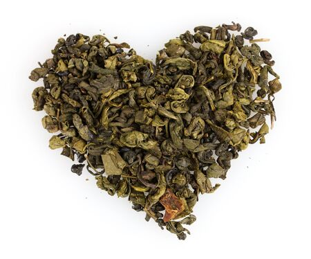 green dry tea heart shape isolated on white photo