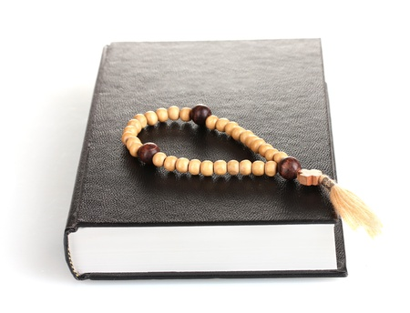 Bible and wooden rosary  isolated on white photo