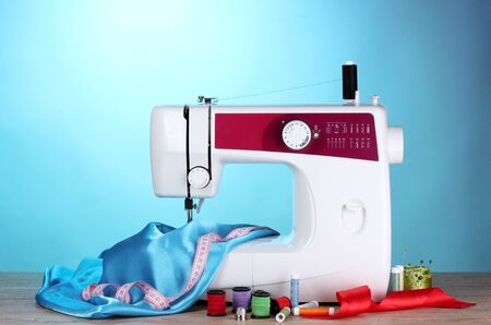 sewing machine and fabric on blue background photo