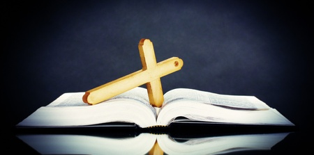 Russian bible and wooden cross on black background Stock Photo - 12217367