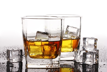 two glasses of scotch whiskey and ice on table isolated on white photo